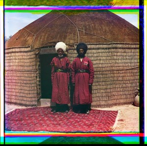 Two men standing on a rug, in front of yurt
